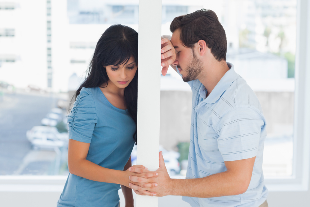 Divided couple are separated by white wall but holding hands