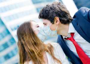 Lovers workers kissing with protective face mask against pollution