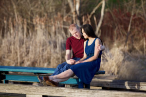 Young interracial couple quietly praying together on wooden pier over water
